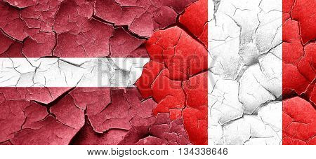 Latvia flag with Peru flag on a grunge cracked wall