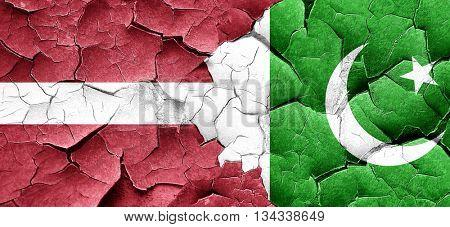 Latvia flag with Pakistan flag on a grunge cracked wall