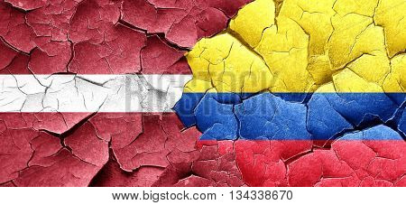 Latvia flag with Colombia flag on a grunge cracked wall