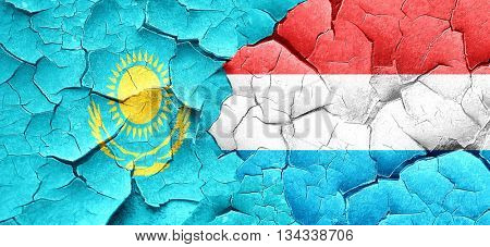 Kazakhstan flag with Luxembourg flag on a grunge cracked wall