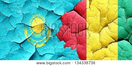 Kazakhstan flag with Guinea flag on a grunge cracked wall