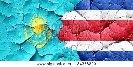 Kazakhstan flag with Costa Rica flag on a grunge cracked wall