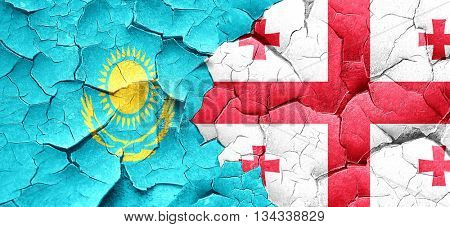 Kazakhstan flag with Georgia flag on a grunge cracked wall