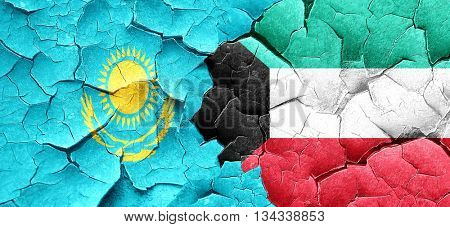 Kazakhstan flag with Kuwait flag on a grunge cracked wall
