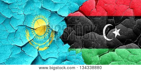 Kazakhstan flag with Libya flag on a grunge cracked wall