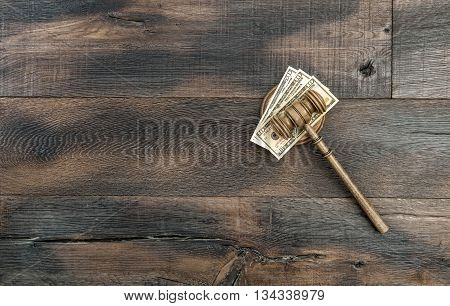 Judges gavel with soundboard and US dollar banknotes. Auctioneer hammer on wooden background