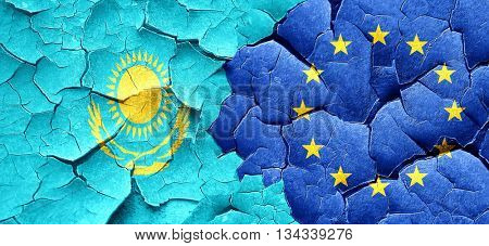 Kazakhstan flag with european union flag on a grunge cracked wal