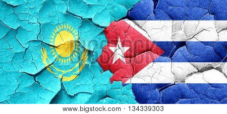 Kazakhstan flag with cuba flag on a grunge cracked wall