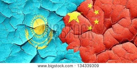 Kazakhstan flag with China flag on a grunge cracked wall