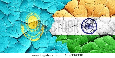 Kazakhstan flag with India flag on a grunge cracked wall