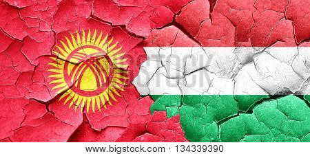 Kyrgyzstan flag with Hungary flag on a grunge cracked wall