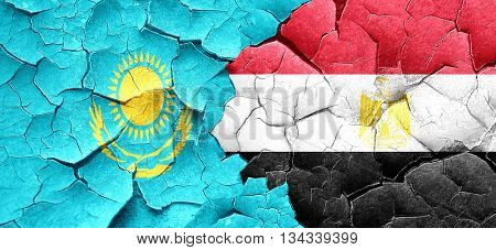Kazakhstan flag with egypt flag on a grunge cracked wall
