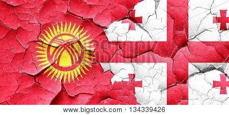Kyrgyzstan flag with Georgia flag on a grunge cracked wall