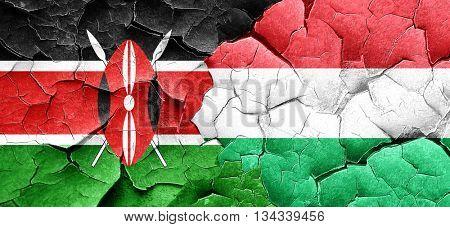 Kenya flag with Hungary flag on a grunge cracked wall