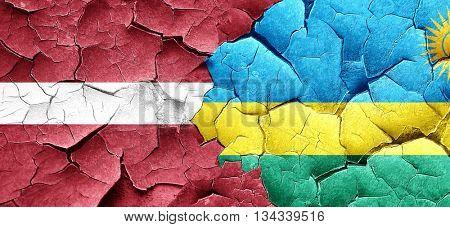 Latvia flag with rwanda flag on a grunge cracked wall