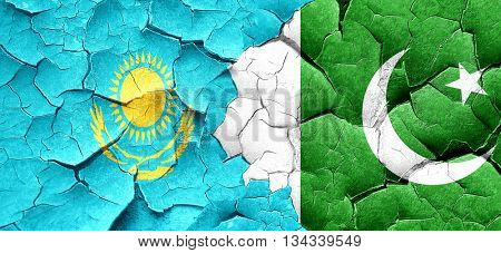 Kazakhstan flag with Pakistan flag on a grunge cracked wall