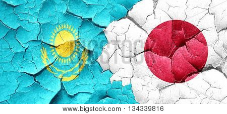 Kazakhstan flag with Japan flag on a grunge cracked wall