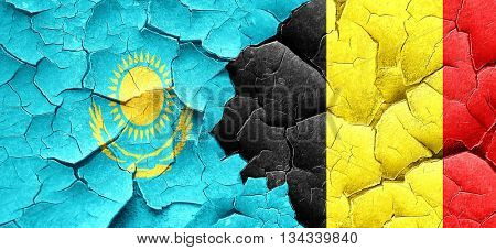 Kazakhstan flag with Belgium flag on a grunge cracked wall