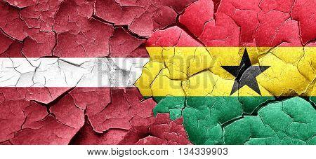 Latvia flag with Ghana flag on a grunge cracked wall