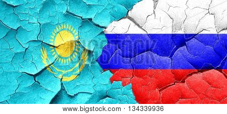 Kazakhstan flag with Russia flag on a grunge cracked wall