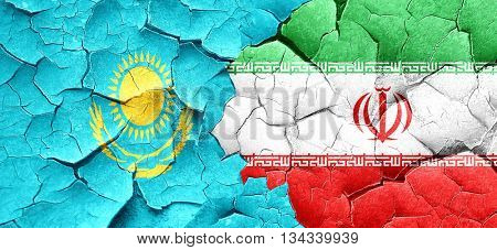 Kazakhstan flag with Iran flag on a grunge cracked wall