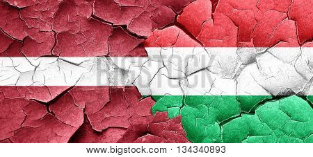 Latvia flag with Hungary flag on a grunge cracked wall