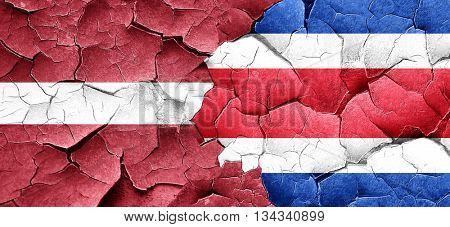 Latvia flag with Costa Rica flag on a grunge cracked wall