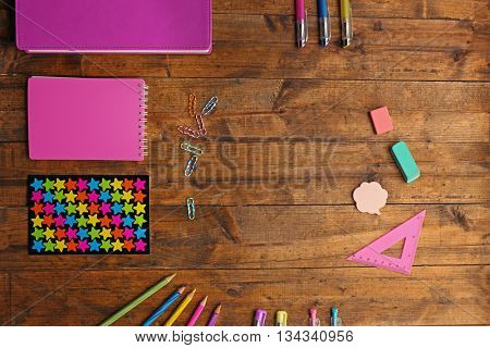 School set with notebooks, colored pens and pencils on wooden background
