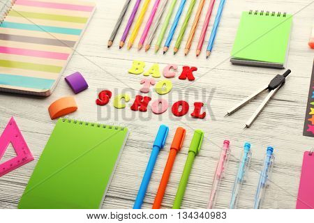 School set with back to school inscription, notebooks on light wooden background