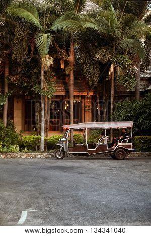 PATTAYA THAILAND - MARCH 22 2016: Hotel tuk-tuk car driver waiting for passenger tourists to take them to city or beach. Thai three wheeled auto rikshaw