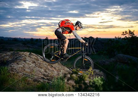 Cyclist Riding the Bike Down Hill on the Mountain Rocky Trail at Sunset