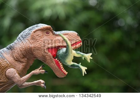 gigantic tyrannosaurus catches a smaller dinosaur in front of trees