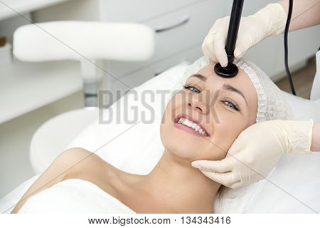 Young pretty woman receiving treatments in beauty salons. poster