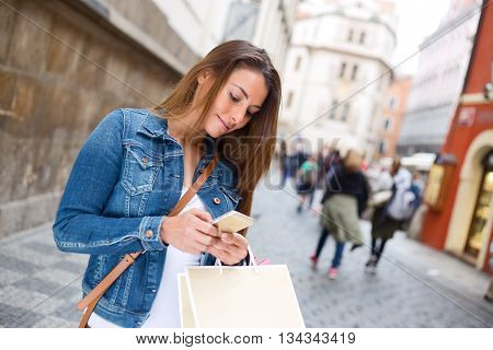 young woman reading her text messages in the street