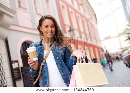 young woman in the street holding shopping bags and a coffee