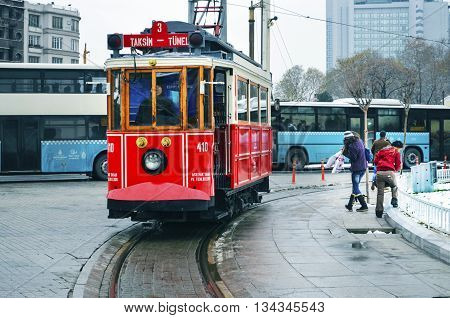 Istanbul Turkey - September 21 2012: the former tram on Istiklal Street in Istanbul Taksim-Tunel carry passengers. A cold winter day.Taksim Square children playing snowballs