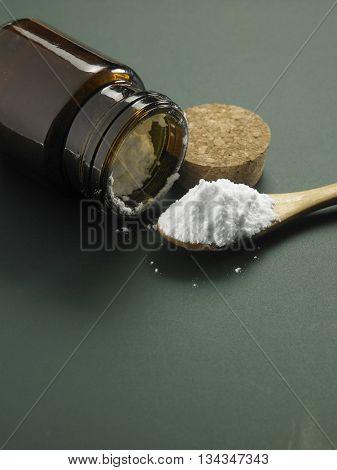 bottle of baking soda with wooden spoon