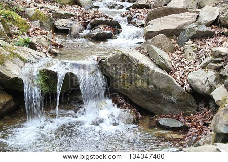 Scenic nature landscape of a river trickling down the rocks from a hill