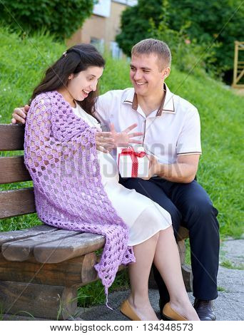 pregnant woman takes a gift from her husband, happy family, couple in city park, summer season, green grass and trees