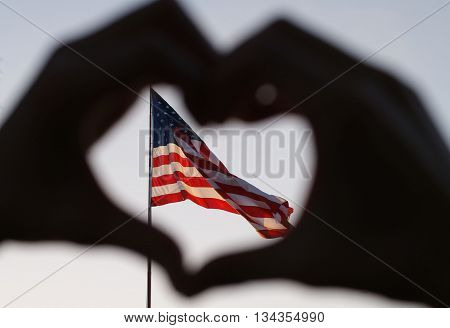 A blurry image of a hand making a heart with the focus on the American Flag.