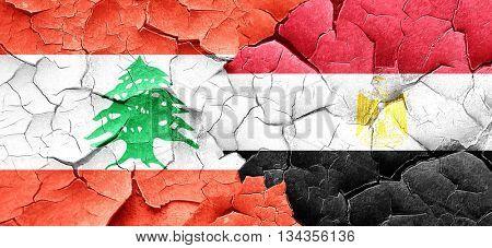 Lebanon flag with egypt flag on a grunge cracked wall