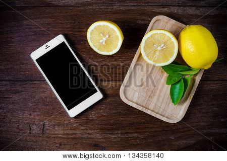 Fresh slice lemons with leaves on wooden background.