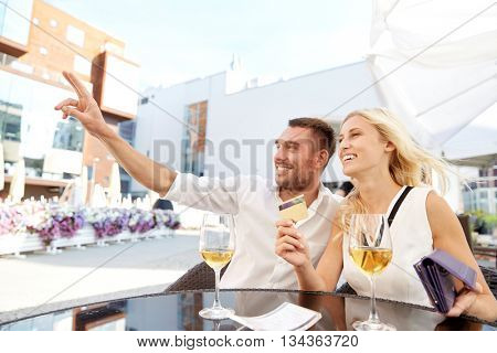date, people, payment and finances concept - happy couple with wallet, credit card and wine glasses calling waiter for bill payment at restaurant