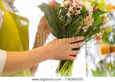 people, business, sale and floristry concept - close up of florist man making bunch at flower shop