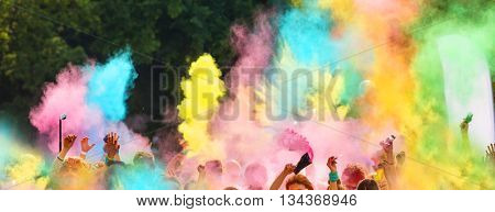 Crowd of people on color run throwing colored powder
