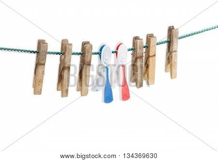Two new plastic clothespins with multi-colored rubber inserts among a several old wooden clothespin on a clothes line on a light background