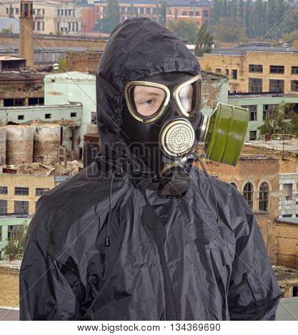 Person in a rubber gas mask and in a black jacket with a hood against the backdrop of abandoned and partially destroyed industrial buildings