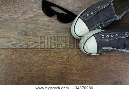 Grey casual shoes and sunglasses on a wooden floor