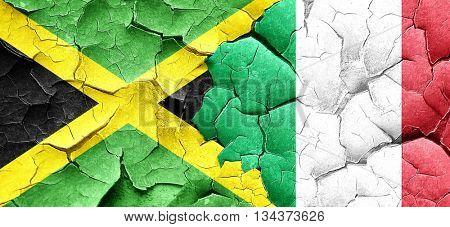 Jamaica flag with Italy flag on a grunge cracked wall