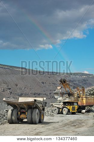 Dump trucks being loaded with iron ore on the opencast mining. Rainbow in the sky on the background